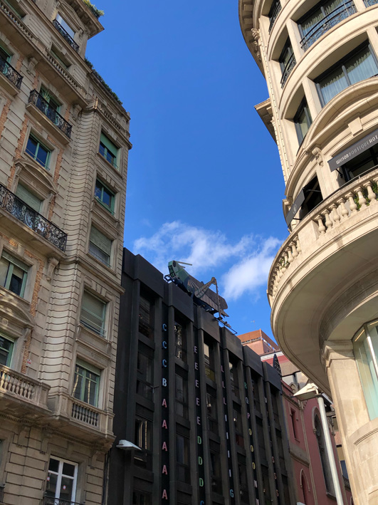 Street view of the giant grasshopper sculpture on top of the Barcelona Surveyors' Association building