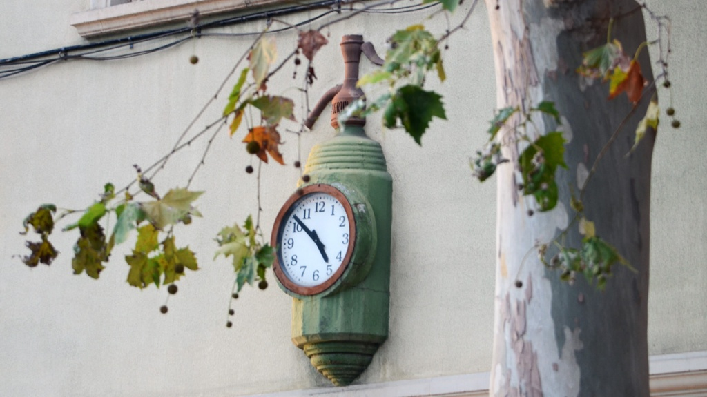 View of Can Puértolas clock through tree's leaves