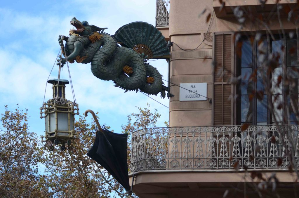 Casa Bruno Cuadros dragon seen hanging from building with lamp and umbrella