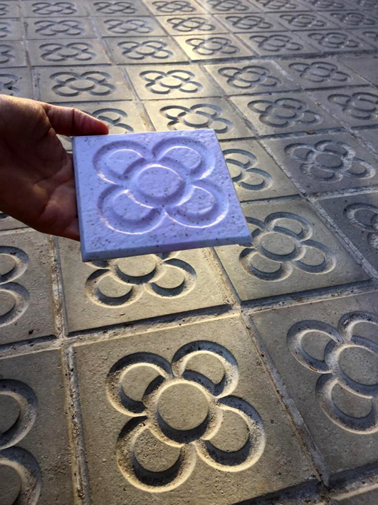 A Canfanga Panots coaster seen held above a sidewalk covered in the Barcelona flower