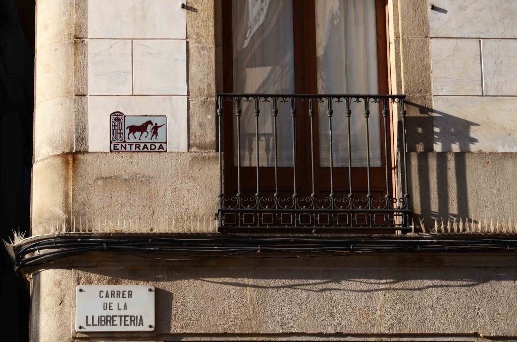 "Old entry sign next to a balcony and above ""Carrer de la Llibreteria"" sign."