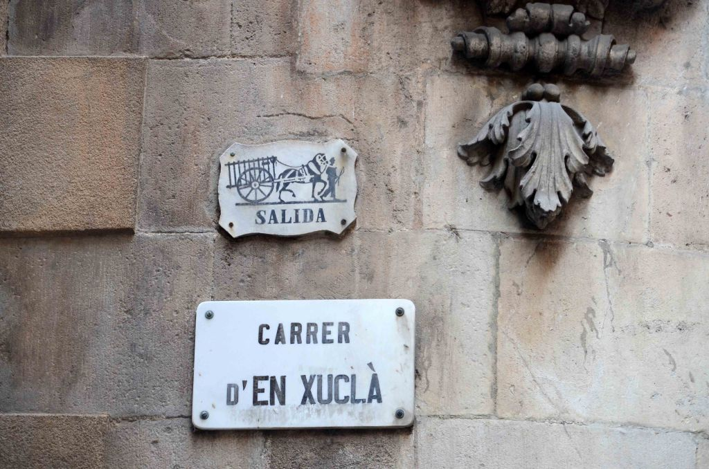 "Old exit sign on building above ""Carrer d'en Xuclà"" sign."