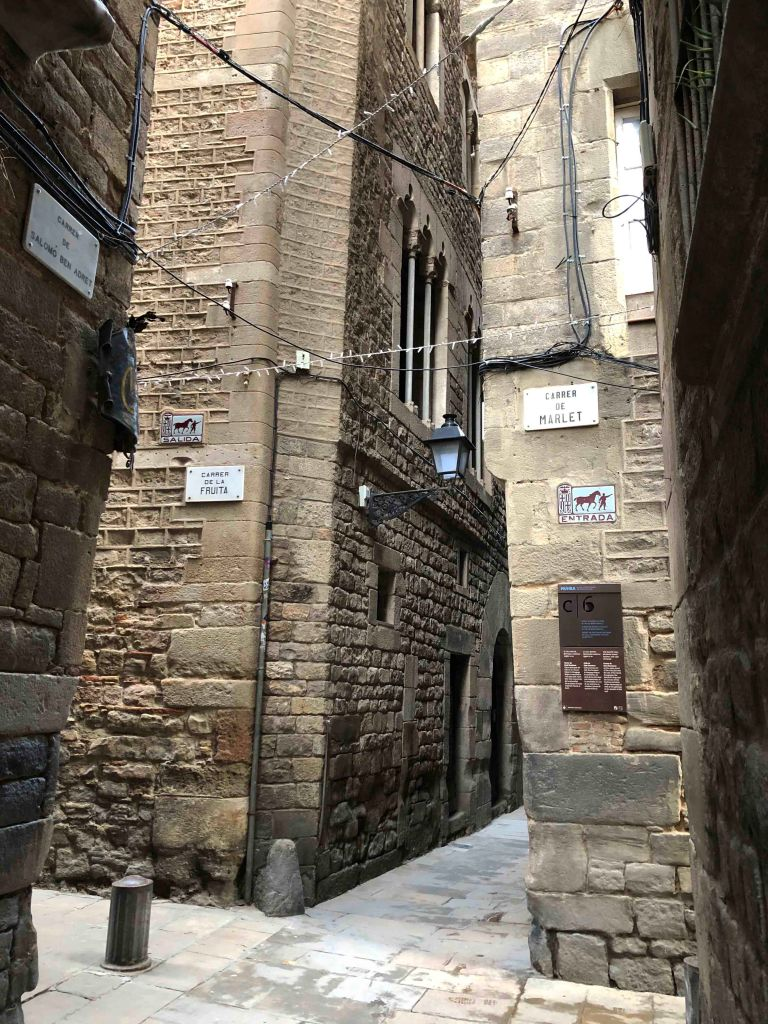 View of Barcelona's narrow Gothic Quarter streets and old entry and exit signs