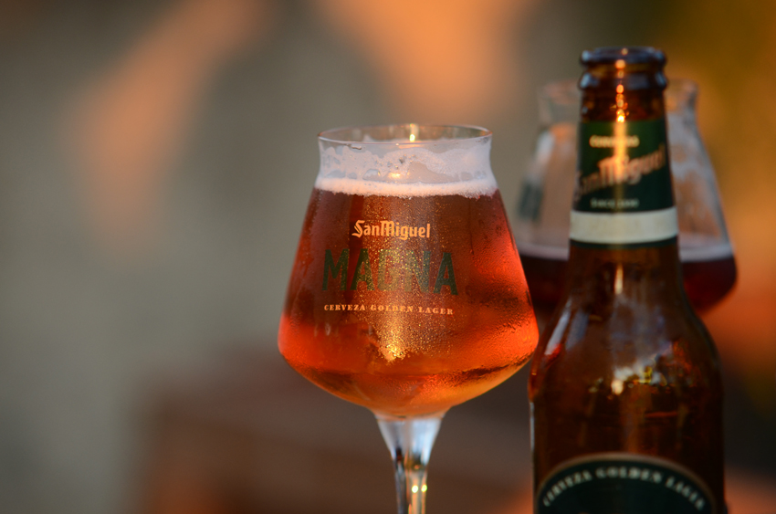Glass of San Miguel Magna beer in light from sunset